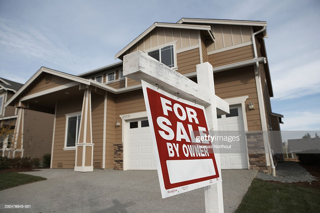 'For Sale' sign in front of house (focus on sign) : Foto stock