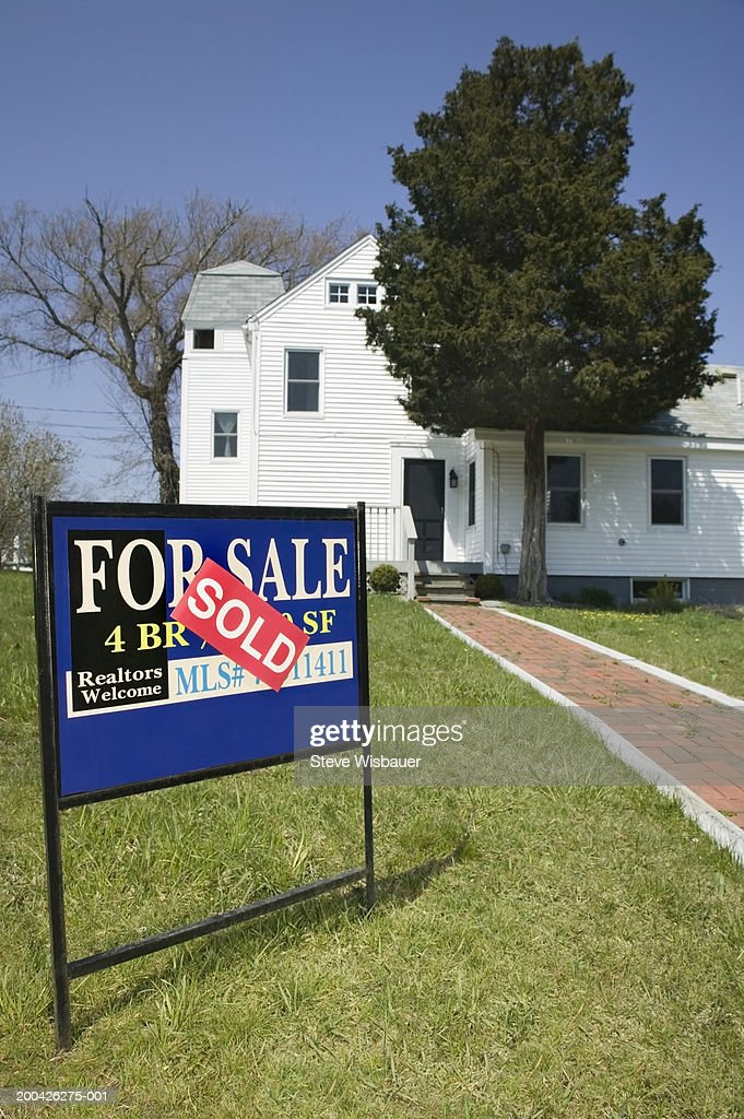 'For Sale' sign on lawn in front of house : Stock Photo