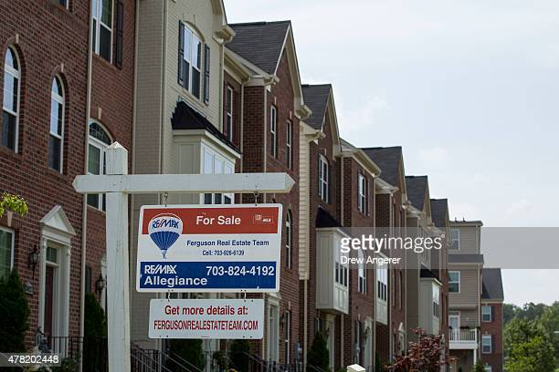 """For Sale"""" sign sits in the front yard of a townhouse June 23, 2015 in Northeast Washington, DC. Purchases of new homes in the U.S. Rose in May to the..."""