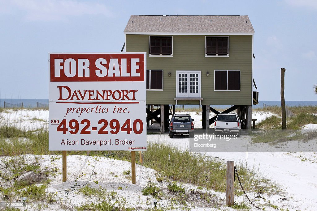 A for sale sign sits outside a beachfront home along the