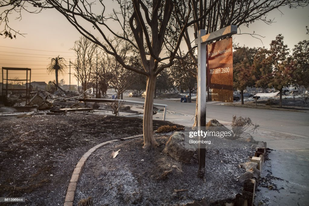A 'For Sale' sign stands in front of residences burned by wildfires in Santa Rosa, California, U.S., on Friday, Oct. 13, 2017. Wildfires that tore through northern California's iconic wine-growing regions have prompted evacuations of more than 20,000 people, killed 11 and damaged some of the most valuable vineyards and wineries in the U.S. About 1,500 commercial, residential and industrial structures were burned, and damage assessment teams have started accounting for the destruction. Photographer: David Paul Morris/Bloomberg via Getty Images