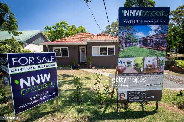 A 'For Sale' sign stands on display outside a house in the suburb of Eastwood in Sydney Australia on Saturday Jan 11 2014 Purchases by locally...