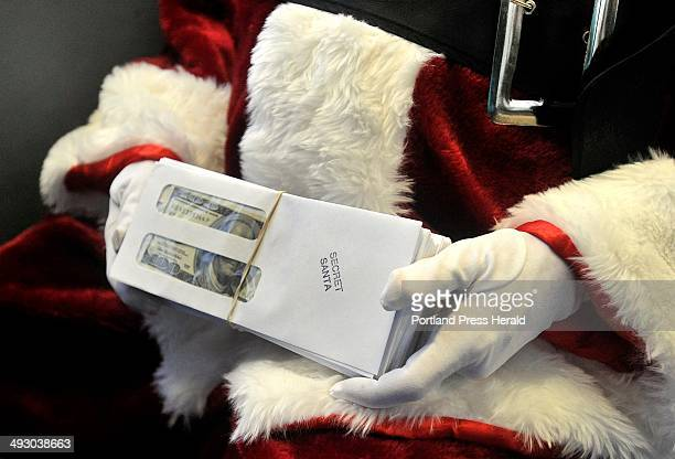 For the fifth year a Secret Santa has continued a tradition of giving out $100 bills to unsuspecting Mainers Santa holds a stack of envelopes...