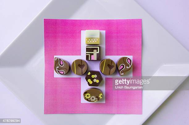 For the palate and the eye Pralines and chokolate as if painted from Swiss production Chocolate on the flag of Switzerland