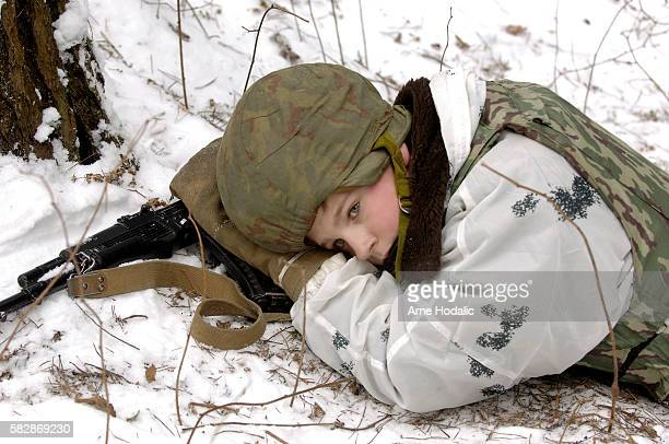 For young participants of the winter camp days can be very exhausting A boy in full combat gear takes a short rest after a long day of training In...