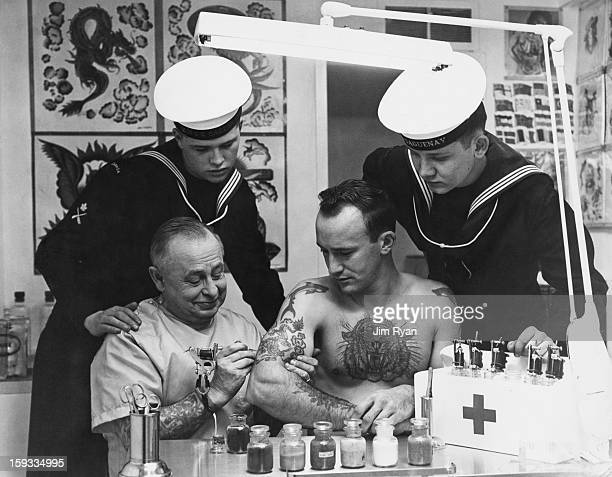 Forbes A Hendry a tattooist in Victoria British Columbia adds the finishing touches to a dragon on the arm of exNavy man Joe Williams February 1965...
