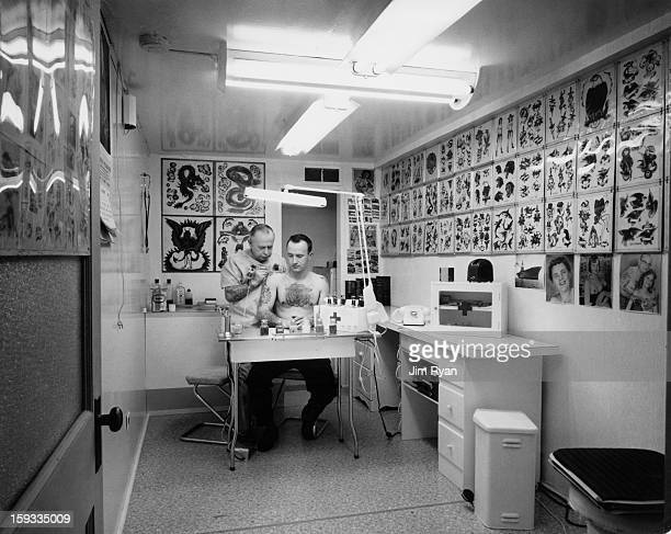 Forbes A Hendry a tattooist in Victoria British Columbia creates an artwork on the shoulder of exNavy man Joe Williams February 1965