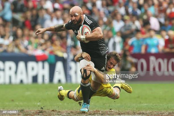 Forbes of New Zealand is tackled during the Cup semifinal match between Australia and New Zealand during day three of the 2014 Hong Kong Sevens at...