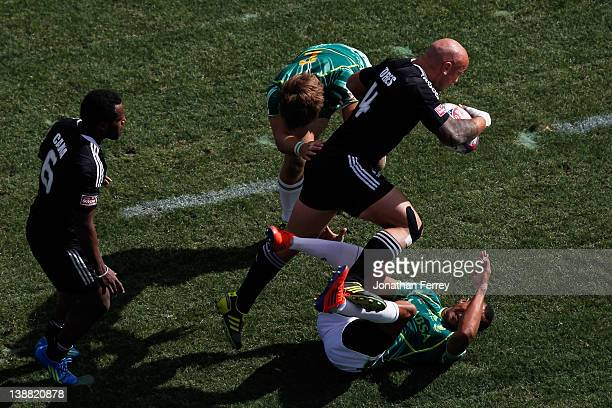 Forbes of New Zealand runs through defenders Cornal Hendricks and Boom Prinsloo of South Africa during the Cup Semi Final on day three of the USA...