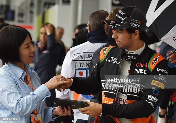 Force India driver Sergio Perez Mendoza of Mexico signs his autograph for a fan prior to the second practice session at the Formula One Japanese...