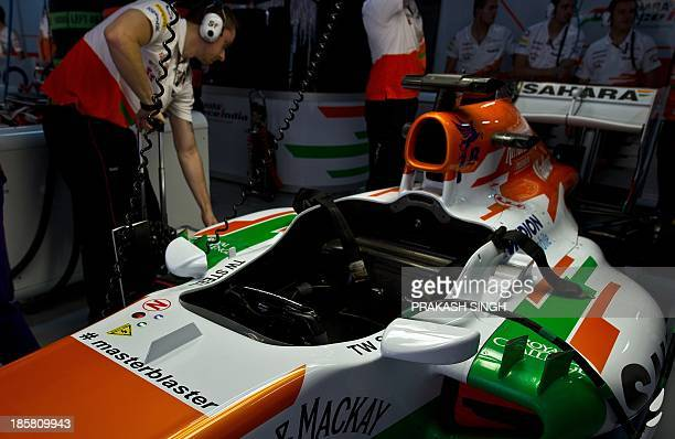 Force India pitcrew prepare the car of Force India driver Paul Di Resta of Britain with the Twitter hashtag '#masterblaster' on his car during the...