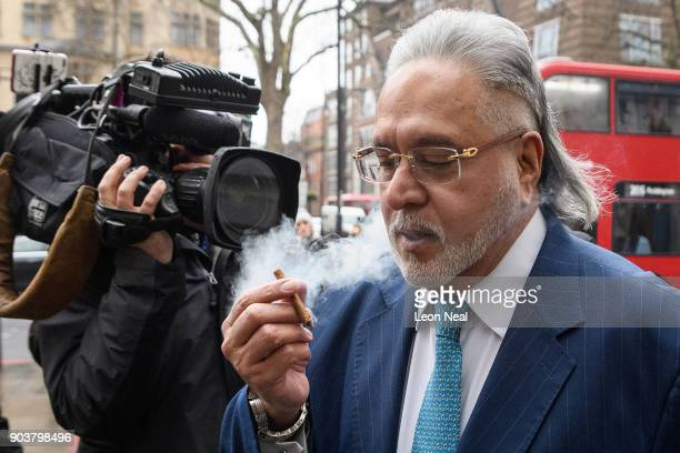 Force India team boss Vijay Mallya walks through the press as he arrives at The City of Westminster Magistrates Court on January 11 2018 in London...