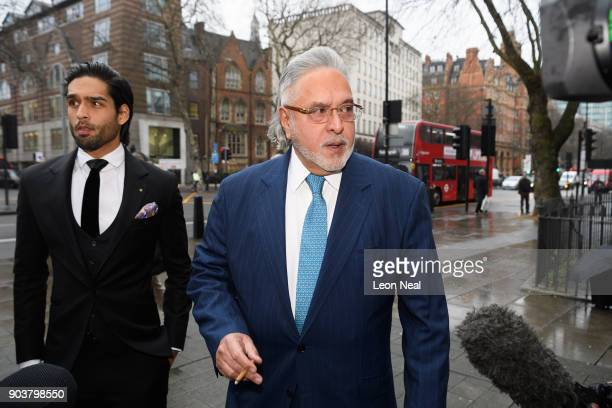 Force India team boss Vijay Mallya walks through the press with his son Siddharth Mallya as he arrives at The City of Westminster Magistrates Court...