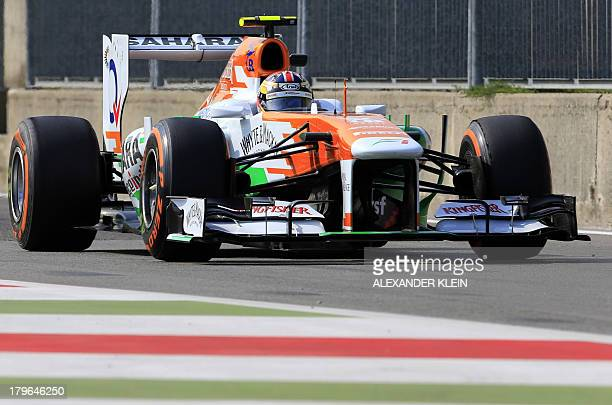 Force India's British test driver James Calado arrives in the pits during the first practice session at the Autodromo Nazionale circuit in Monza on...