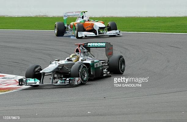 Force India's Scottish driver Paul di Resta and Mercedes' German driver Michael Schumacher drive at the SpaFrancorchamps circuit on August 28 2011 in...