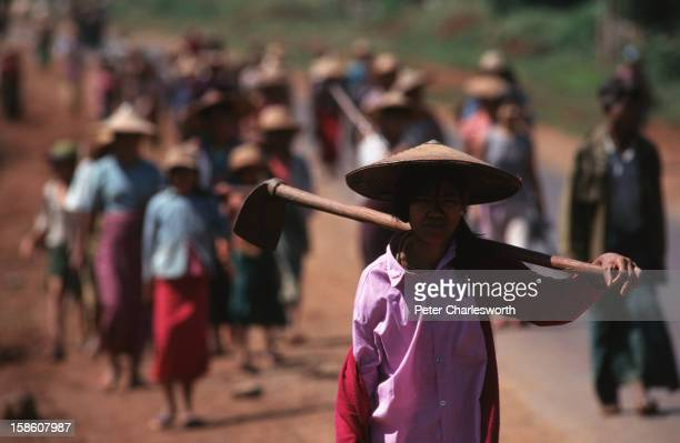 Forced labour or social action Villagers walking down the main road north of Maymyo They have been working on a government road cleanup project near...
