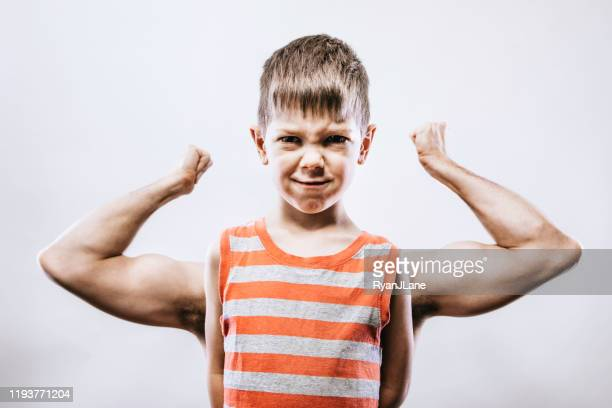 forced perspective flexing strong boy portrait - optical illusion stock pictures, royalty-free photos & images