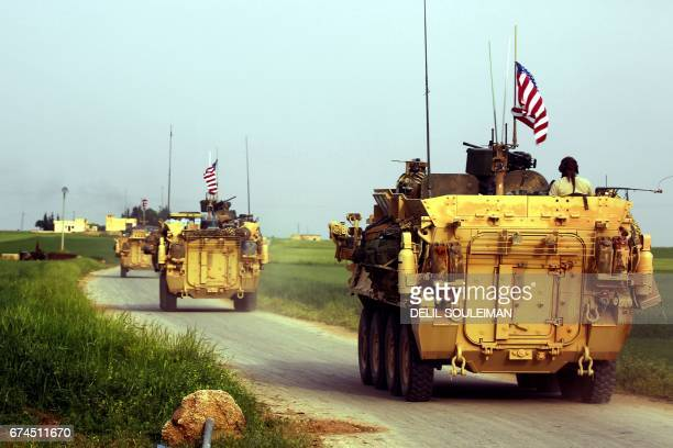 US forces accompanied by Kurdish People's Protection Units fighters drive their armoured vehicles near the northern Syrian village of Darbasiyah on...