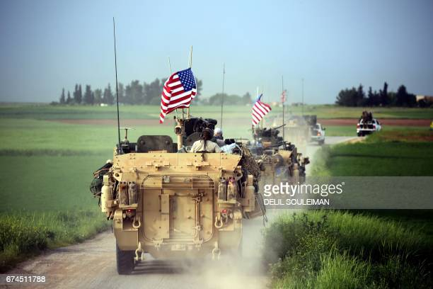 TOPSHOT US forces accompanied by Kurdish People's Protection Units fighters drive their armoured vehicles near the northern Syrian village of...