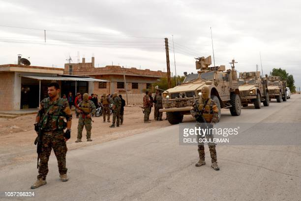 US forces and members of the Syrian Democratic Forces patrol the Kurdishheld town of AlDarbasiyah in northeastern Syria bordering Turkey on November...