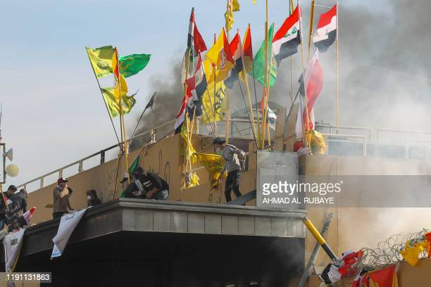US forces fire teargas canisters at supporters and members of the Hashed alShaabi paramilitary force during a demonstration outside the US embassy in...