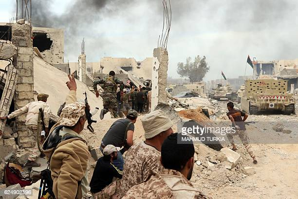 TOPSHOT Forces loyal to Libya's Government of National Accord hold a position amid the rubble of destroyed buildings in Sirte's AlGiza AlBahriya...