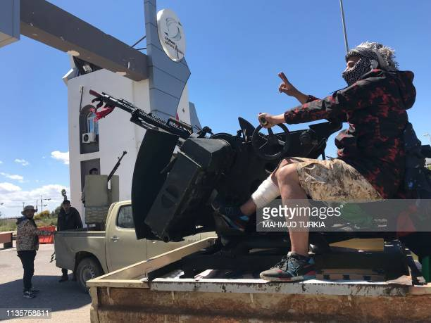 TOPSHOT Forces loyal to the internationally recognised Libyan Government of National Accord are pictured at the entrance gate leading to Tripoli's...