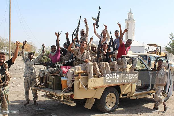 Forces loyal to the Saudibacked Yemeni president flash their arms at a road on the entrance to Abyan province as they take part in an operation to...
