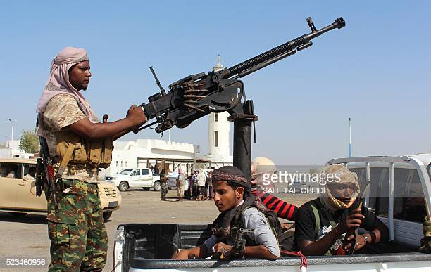 Forces loyal to the Saudibacked Yemeni president stand on the back an armed vehicle on a road leading to the entrance of Abyan province as they take...