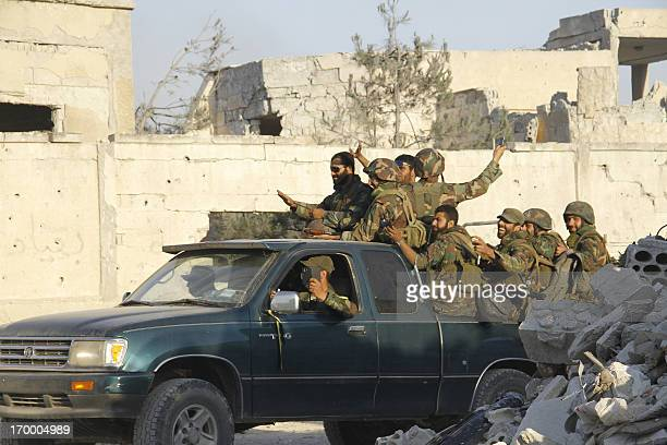 Forces loyal to the Syrian army celebrate as they drive through the ravaged streets of Qusayr in Syria's central Homs province on June 5 after...