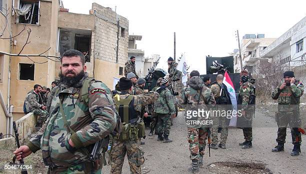 Forces loyal to the Syrian regime stand on a street with national flags after Syria's army and allied forces took full control from rebel groups of...