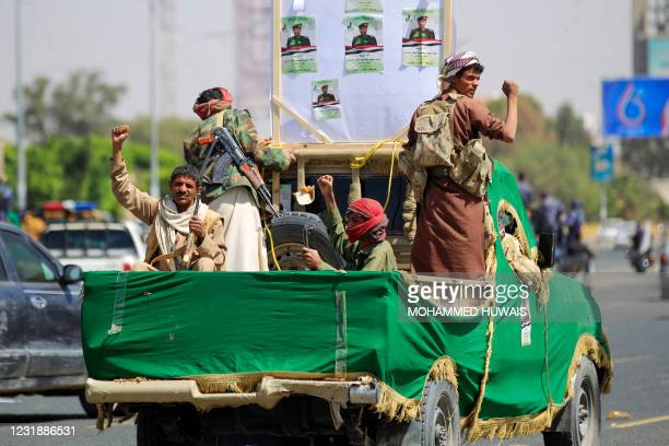 Forces loyal to Yemen's Huthi rebels shout slogans during a mass funeral for fighters killed in battles with Saudi-backed government troops in the...