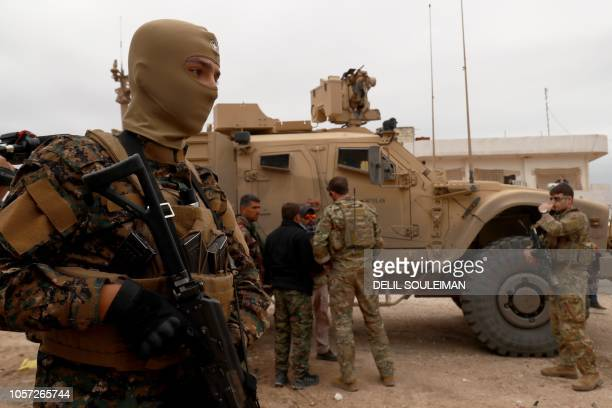 US forces patrol the Kurdishheld town of AlDarbasiyah in northeastern Syria bordering Turkey on November 4 2018 Three armoured vehicles carrying...