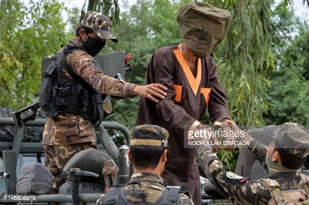 Forces with Afghanistan's National Directorate of Security escort an alleged militant as Taliban and Islamic State fighters are presented to the...