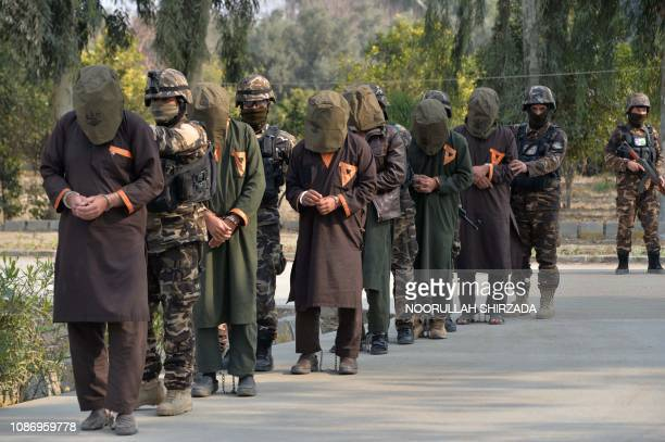Forces with Afghanistan's National Directorate Security escort alleged Taliban fighters after they are presented to media in Jalalabad on January 23...