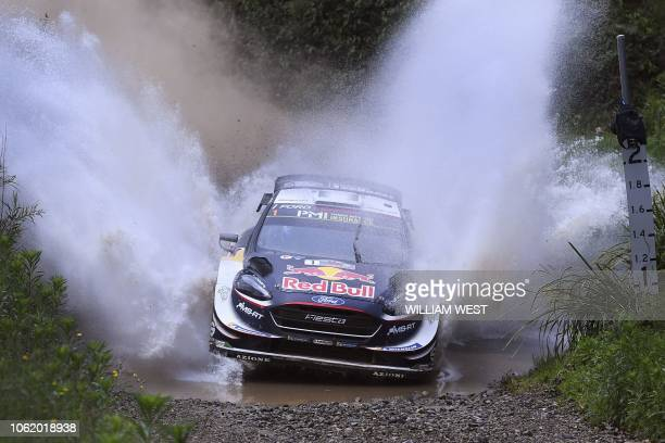 TOPSHOT Ford driver Sebastien Ogier of France speeds through a creek on the first day of the World Rally Championship Rally Australia near Coffs...