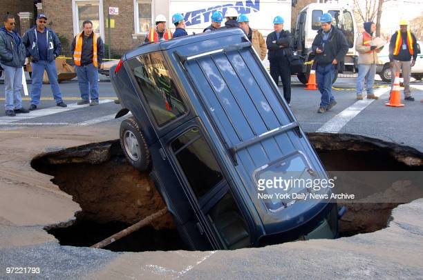 Ford Explorer sits nosefirst inside a 15footby20footwide sinkhole at the intersection of Fourth Ave and 73rd St in the Bay Ridge section of Brooklyn...