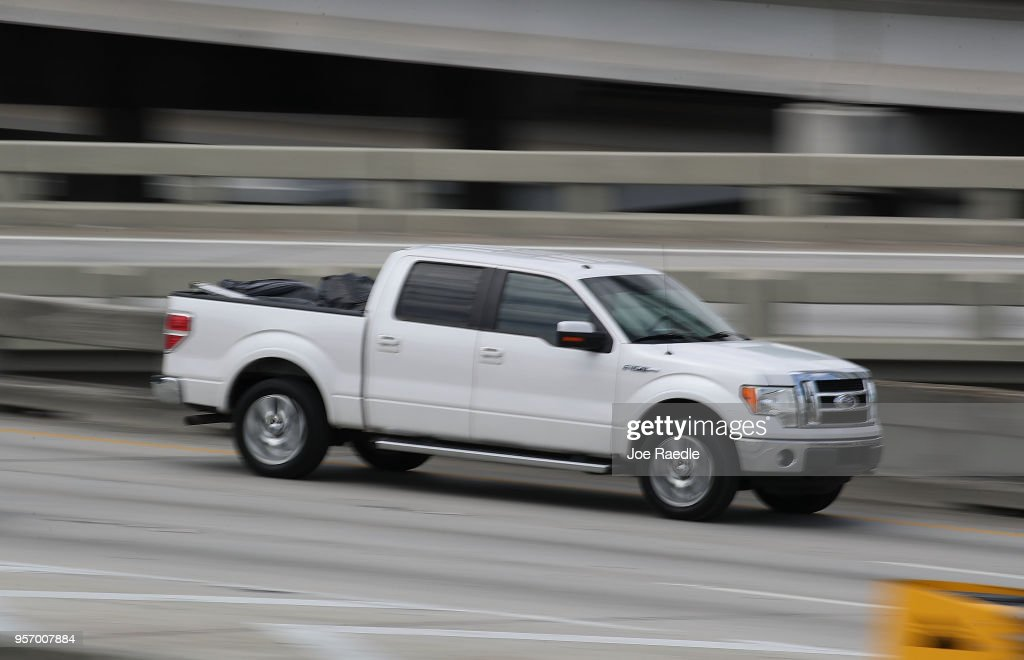 A Ford F-150 pickup truck is seen being driven along a road on May 10, 2018 in Miami, Florida. The company announced it is suspending production of its F-150 trucks after a fire at a supplier's facility caused it to run out of some parts needed in the production of the truck.