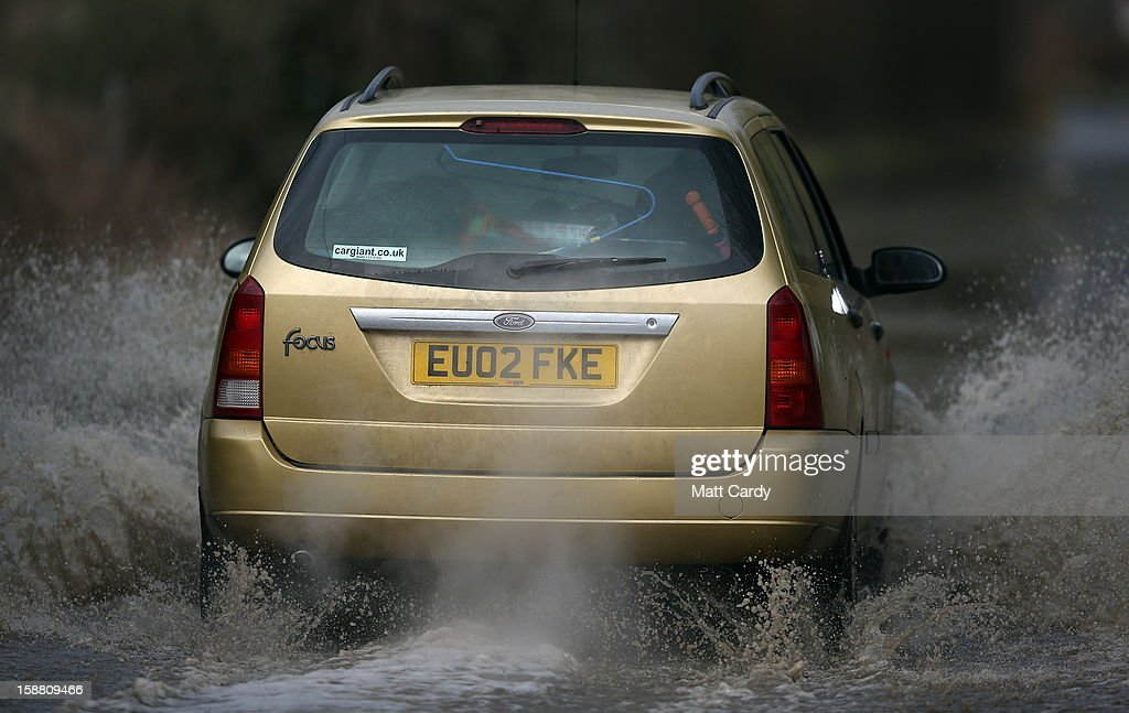 A Ford Focus estate car drives through flood waters surrounding the village of Muchelney, which has been cut off by flooding on the Somerset Levels, on December 30, 2012 near Langport, England. The Met Office is warning of the risk of further flooding towards the end of the year, meaning 2012 is set to be the wettest on record.