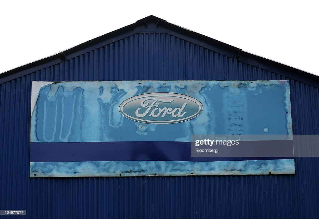 A Ford logo hangs from a building at the Ford Motor Co. automobile plant in Dagenham, U.K., on Monday, Oct. 29, 2012. Ford Motor Co. will shut three European plants, its first factory closings in the region in a decade, and cut 5,700 jobs to stem losses that the carmaker predicts will total more than $3 billion over two years. Photographer: Simon Dawson/Bloomberg via Getty Images
