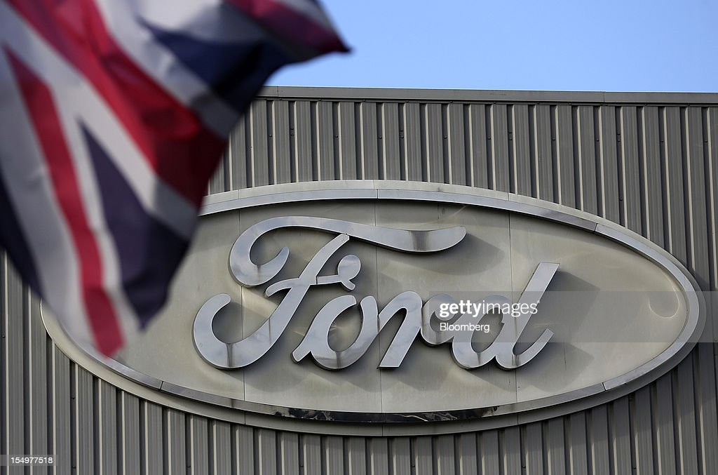 A Ford logo is seen on a stamping operations building near a Union Jack flag at the Ford Motor Co. automobile factory in Dagenham, U.K., on Monday, Oct. 29, 2012. Ford Motor Co. will shut three European plants, its first factory closings in the region in a decade, and cut 5,700 jobs to stem losses that the carmaker predicts will total more than $3 billion over two years. Photographer: Simon Dawson/Bloomberg via Getty Images