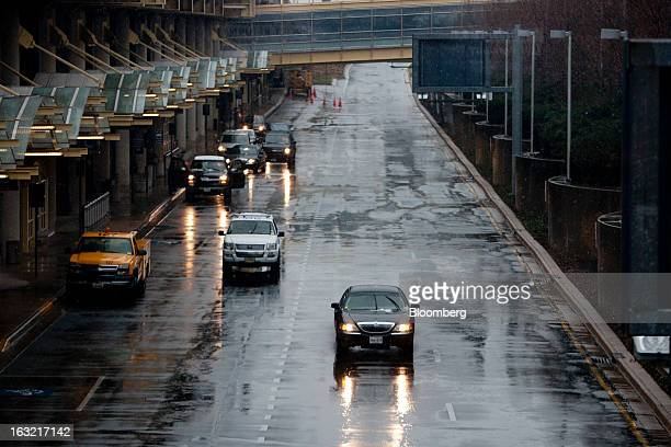 A Ford Motor Co Lincoln Town Car travels through Reagan National Airport in Washington DC US on Wednesday March 6 2013 Light snow mixed with rain...