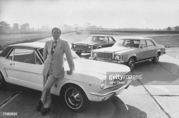 Ford Motor Co President Lee A Iacocca leaning against a Ford Mustang
