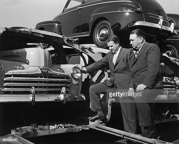 Ford Motor Company CEO Henry Ford II and vicepresident of manufacturing ML Bricker inspect a haulaway loaded with 1946 Ford cars at the Ford River...