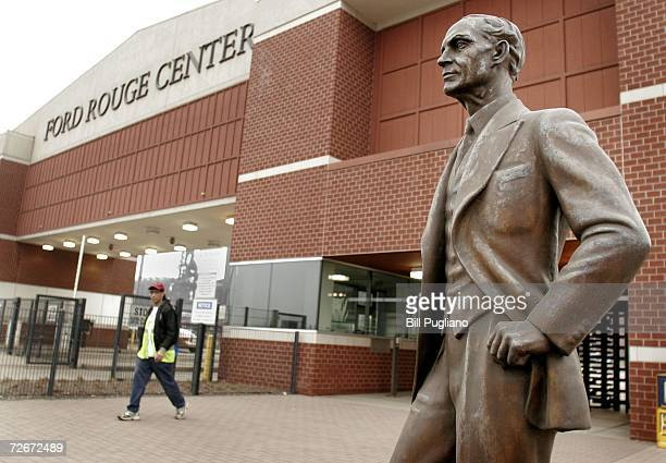 Ford Motor Company employee exits out the front gate of the Ford Rouge Plant behind a statue of Henry Ford November 29 2006 in Dearborn Michigan A...