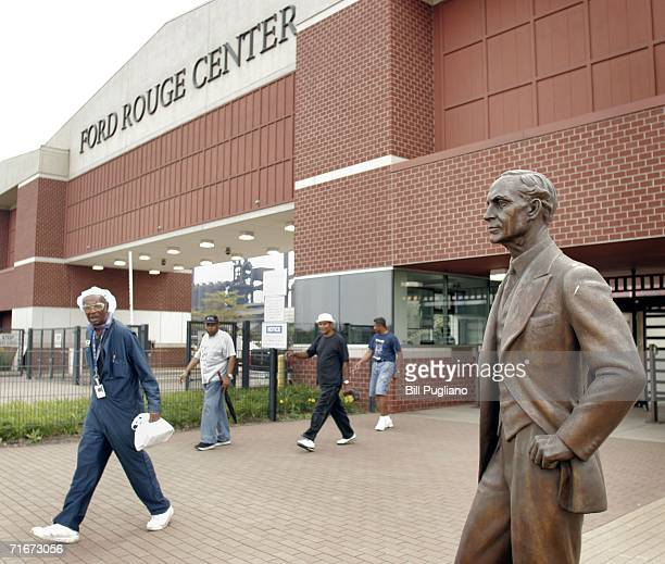 Ford Motor Company employees leave the Ford Dearborn Truck Assembly Plant at the end of their shift under the gaze of a statue of Ford founder Henry...