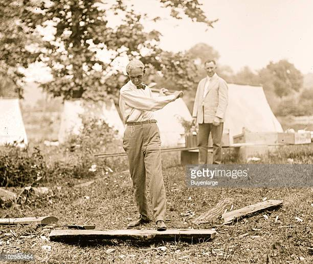 Ford Motor Company founder Henry Ford chopping wood, possibly during a camping trip with Thomas Edison, 1921.