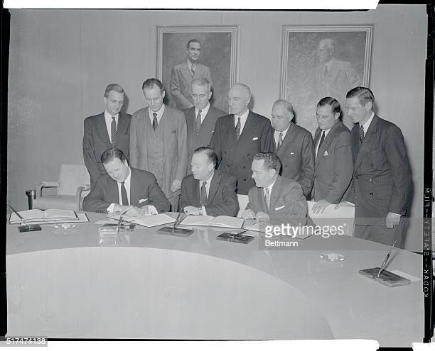 Ford Motor Company President Henry Ford II signs the historic agreement between the Ford Foundation and a group of underwriters who are handling the...
