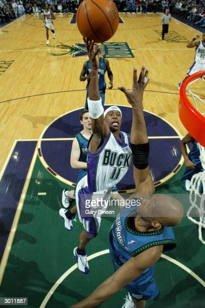 J Ford of the Milwaukee Bucks shoots over Sam Cassell of the Minnesota Timberwolves February 24 2004 at the Bradley Center in Milwaukee Wisconsin...