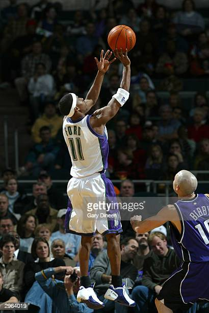 J Ford of the Milwaukee Bucks takes a jump shot while Mike Bibby of the Sacramento Kings looks on during the game on February 10 2004 at the Bradley...